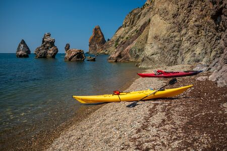 Two kayaks yellow and red on the shore of a small shingle wild beach against the background of rocks in the sea, Fiolent, Crimea