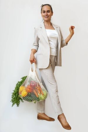 A woman in a light suit holds a cotton shopper and reusable mesh shopping bags with vegetables. Zero waste without plastic concept with copy space. Eco-friendly net buyer.