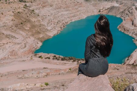 A brunette girl with loose hair in a gray dress sits on the background of an azure lake in the form of a heart, rear view 写真素材