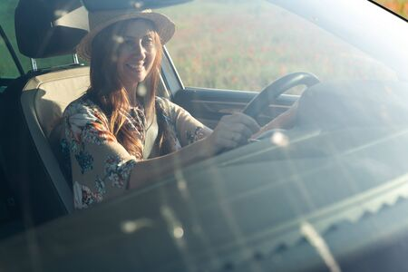A smiling woman in a hat and colored dress sits behind the wheel of a car, behind the windshield. In the window blooming field of poppies. Stock Photo
