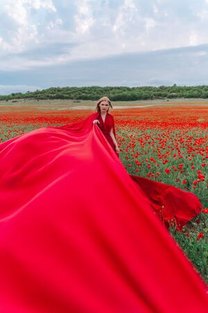 A young blonde looks forward in a red dress and long red stripes of fabric posing on a large field of red poppies