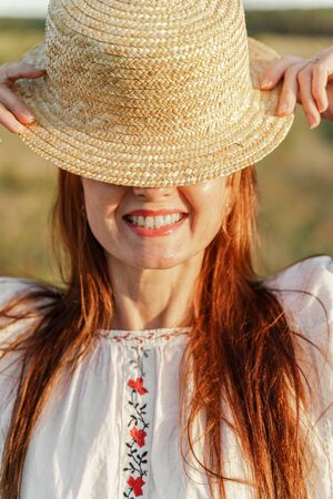 A red-haired smiling woman holds a hat in her hands, only the bottom of her face with a smile is visible. On a green field.
