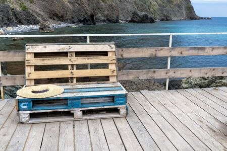 Standard wooden furniture made of cargo pallets, painted in places in blue color on the beach on a wooden platform with railings. Rocks are visible in the sea. Front view 免版税图像