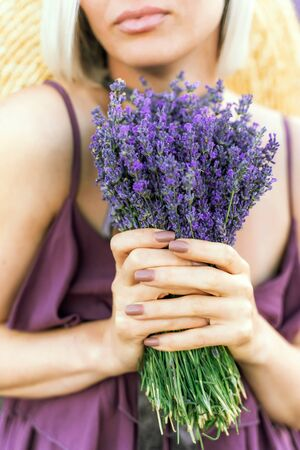 Blonde in a purple dress holds a bouquet of lavender. You can see the lips and hands, on a sunny bright day. The concept of aromatherapy, spa, appeasement.