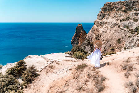 A woman in a white flying dress is seen behind, fluttering in the wind. In a straw hat, walking along the path. The concept of travel 免版税图像