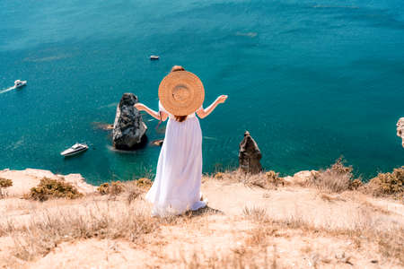 From behind, a woman is seen in a white flying dress fluttering in the wind. In a straw hat, walking down the stairs against the background of the sea with rocks and boats. The concept of travel 免版税图像
