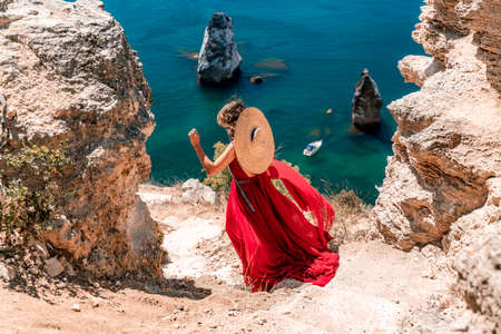 From behind, a woman is seen in a red flying dress fluttering in the wind. In a straw hat, walking down the stairs against the background of the sea with rocks and boats. The concept of travel