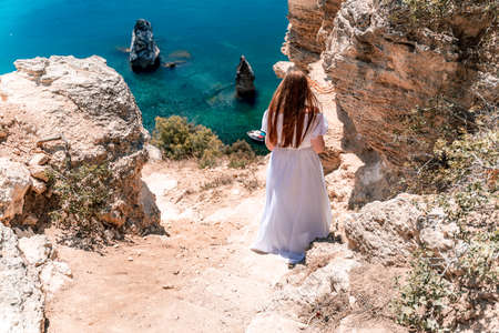 A woman in a white flying dress is seen behind, fluttering in the wind. Going down the stairs against the background of the sea with rocks and boats. The concept of travel