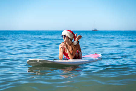 A girl riding a wave on top of a body of water. A woman in a red bikini and a Santa hat lies on a SUP board with the sea and a yacht floating on the horizon. He looks away and smiles Stock Photo