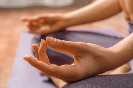 Young woman meditating in the lotus pose at home. Practicing yoga indoors. Harmony, yoga practice, balance, meditation, relaxation at home, healthy lifestyle concept. Imagens