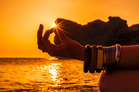 Young womans hand in bracelets. Practice yoga on the beach with sunset. Keeps fingers connected, the sun shines through them. The concept of a healthy lifestyle, harmony. Standard-Bild