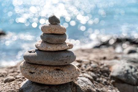 Tower of stones. Balanced pebble pyramid on the beach on a sunny day. Blue sea on the background. Selective focus, bokeh. Zen stones on the sea beach, meditation, spa, harmony, tranquility, balance concept.