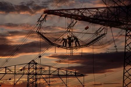 Arbeiten an Strommasten im Sonnenuntergang Standard-Bild - 16868201