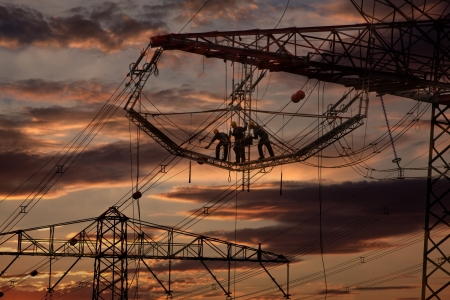 Dolgozik, villanyoszlopok a naplementében Stock fotó