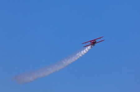 Red biplane smoking at air show Editorial
