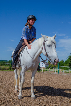 woman is petting a white horse photo