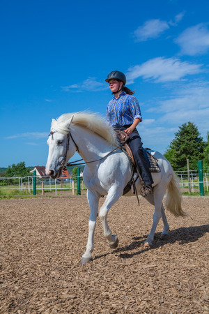young woman is riding a white horse photo