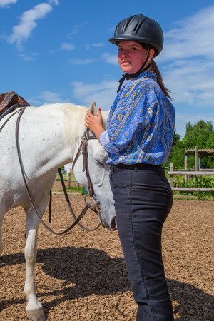 young woman is caressing a white horse photo