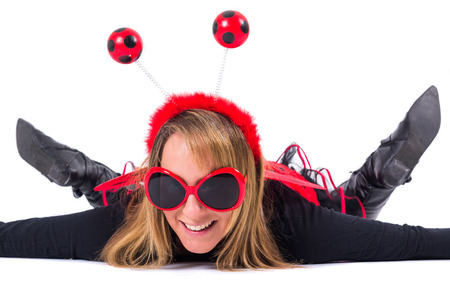 coccinellidae: Lady in bug costume lies on ground Stock Photo