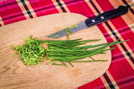 cebollin: cebolletas frescas cortadas con knive en la mesa