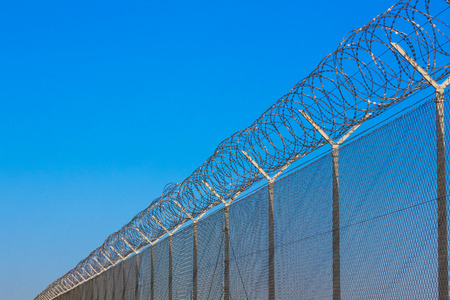 barbed hook wires: barbed wire on a long fence Stock Photo