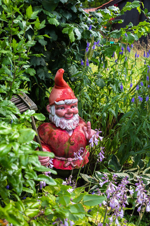 gnome: red garden gnome stands in a garden