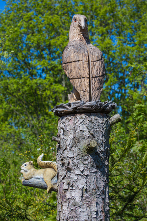 eagle and squirrel sculpture on a tree stem Stock Photo