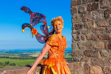 laughing woman as fairy in orange dress