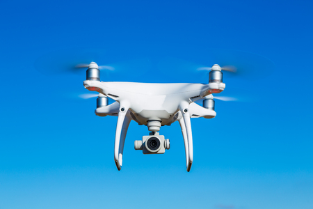 drone flying in blue sky takeing pictures and films Stock Photo