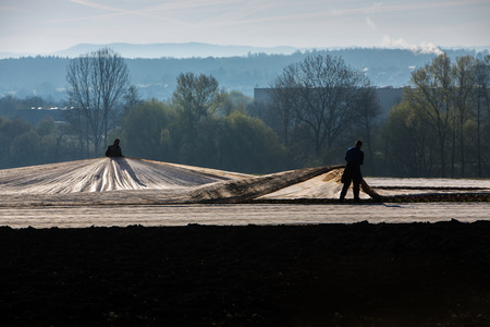 farm workers placing foil on soil in the morning Stock fotó