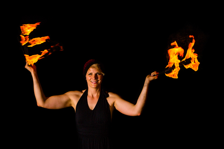 smiling woman holds torches in the dark