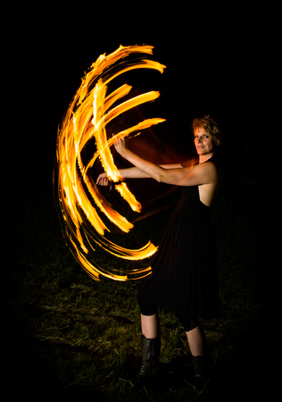 woman shows fire flares in the dark in a performance