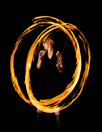 woman displays fire circles in the dark