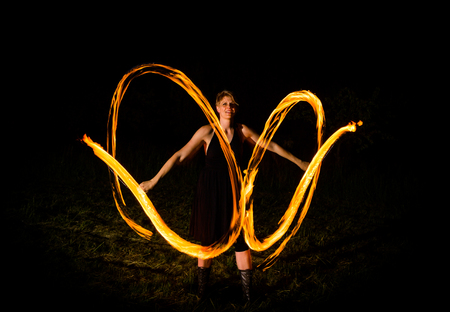 woman displays fire show in the darknes