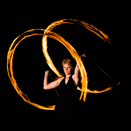 woman is juggling with burning torches