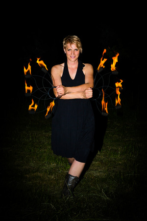 woman shows a performance with torches in the dark