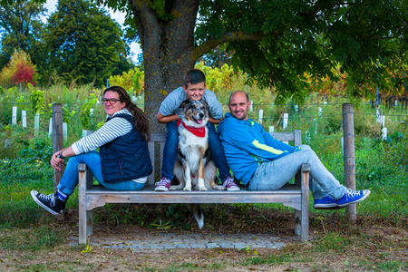 family and dog take a rest on a park bench under  a tree Standard-Bild - 116771327