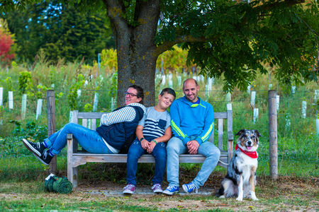 family takes a rest on a park bench under  a tree Standard-Bild - 116771335
