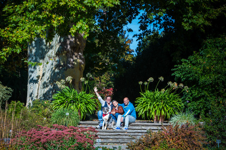 young family with child and dog sitting on stairs in a park Stock fotó