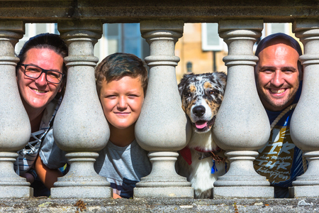 portrait of a family with dog at a fence at castle Hohenheim Stock fotó