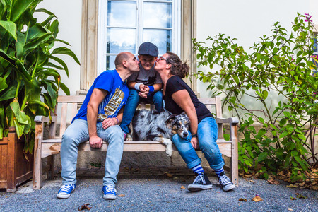 child gets a kiss from his parents on a park bench Standard-Bild - 116772271