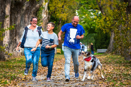 young family with child and dog running in a park with fun