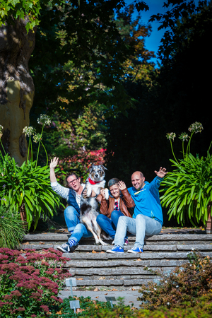 young family with child and dog sitting on stairs in a park Standard-Bild - 116772569