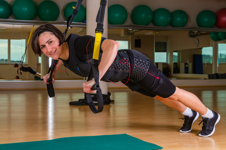 push up exercise of a young woman in a gym