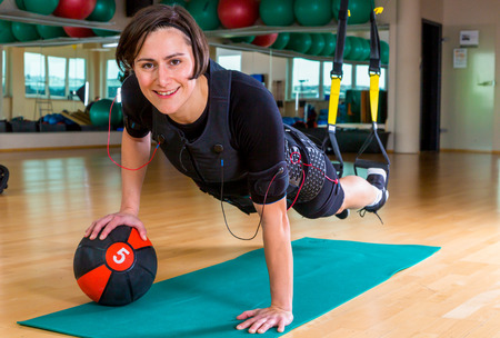 young woman exercising with medicine ball and TRX lash in gym