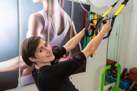 portrait of a young woman stretching in a gym