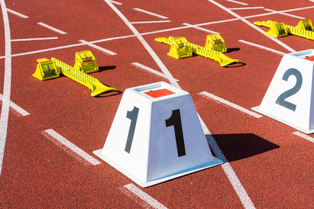 sprint start line in athletic stadium with the numbers one and two Stock fotó