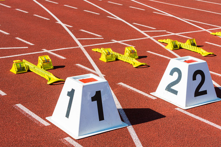 sprint start line in athletic stadium with the numbers one and two Banco de Imagens