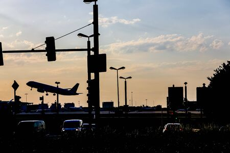 traffic and airplane at evening against the sun Banco de Imagens