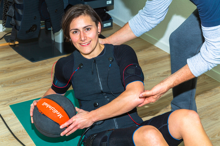 young woman doing a work out with medicinal ball and helping hands